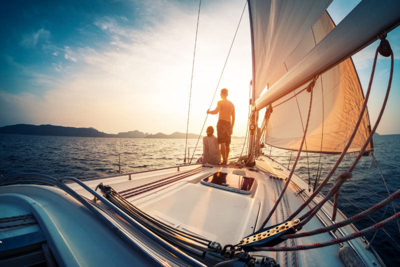 A couple sailing into a sunset