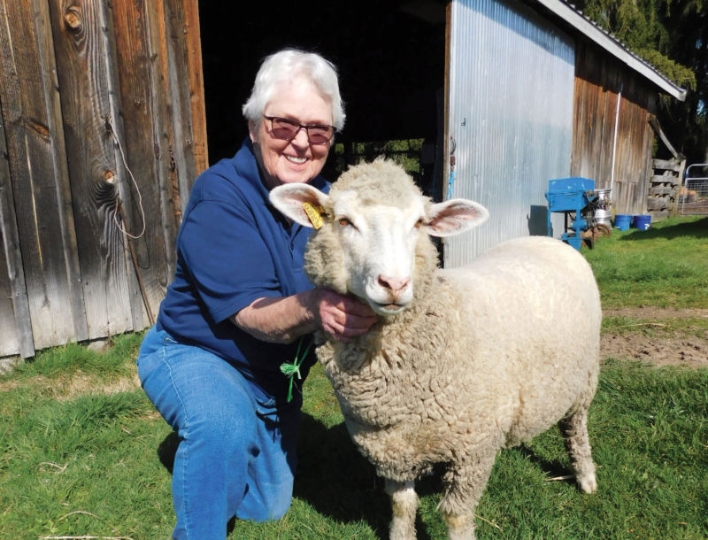 Alice Mattson holding her sheep, in front of her barn