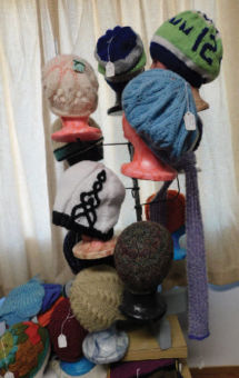 Different colored wool hats on mannequin headss